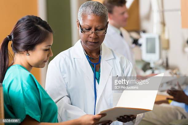 Senior female doctor reviewing patient chart with nurse in hospital
