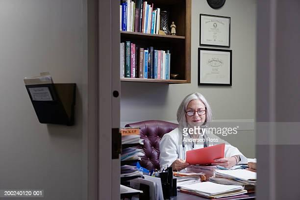 Senior female doctor sitting at desk in office, reading medical file