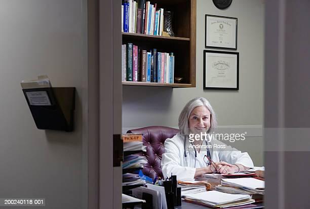 Senior female doctor sitting at desk in office, smiling, portrait