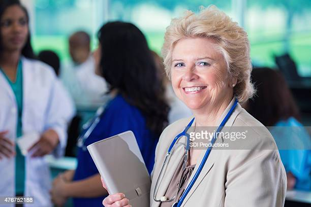 Senior female doctor smiling while attending conference for hospital professionals