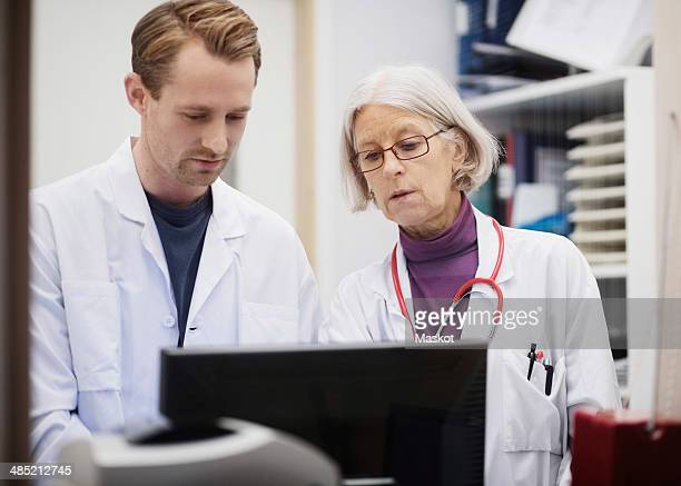 Senior female doctor with male colleague using computer in examination room