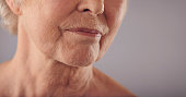 Macro of a senior female face with wrinkled skin against grey background. Cropped old woman face.