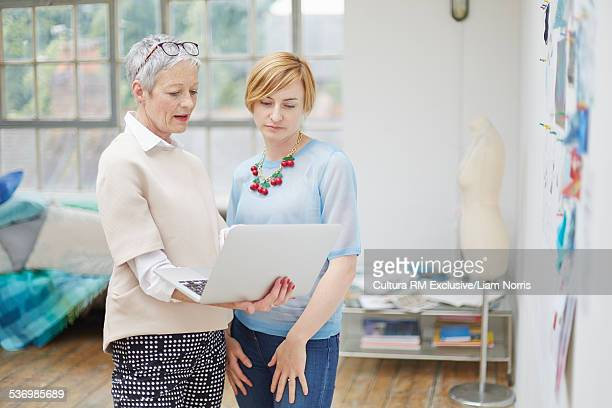 Senior female fashion designer and client looking at laptop