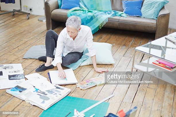 Senior female fashion designer sitting on floor sketching ideas