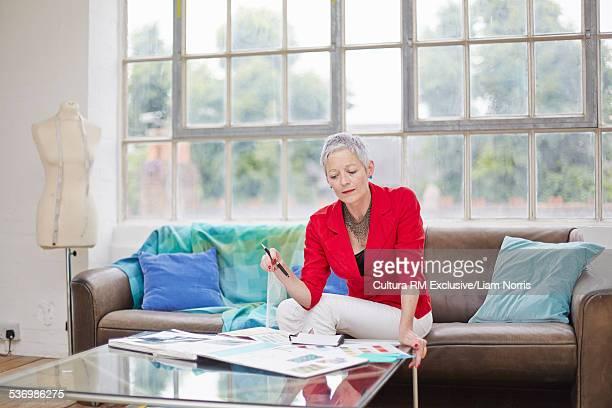 Senior female fashion designer sitting on sofa looking at ideas
