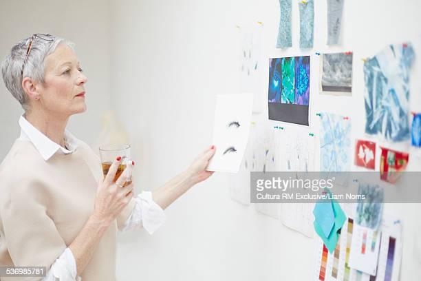 Senior female fashion designers pinning ideas onto wall