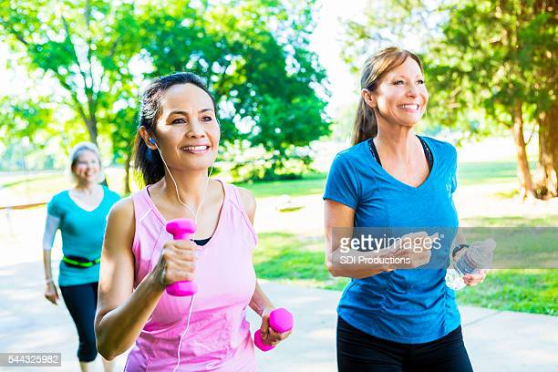 Senior female friends exercise together in park