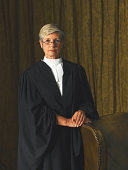 Senior female judge standing by leather chair, portrait