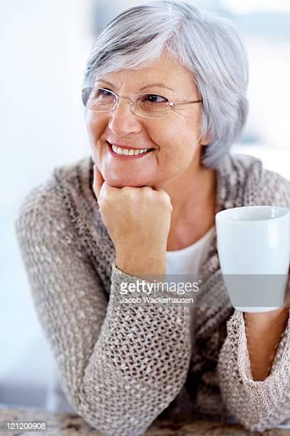 Senior donna guardando qualcosa di interessante con caffè