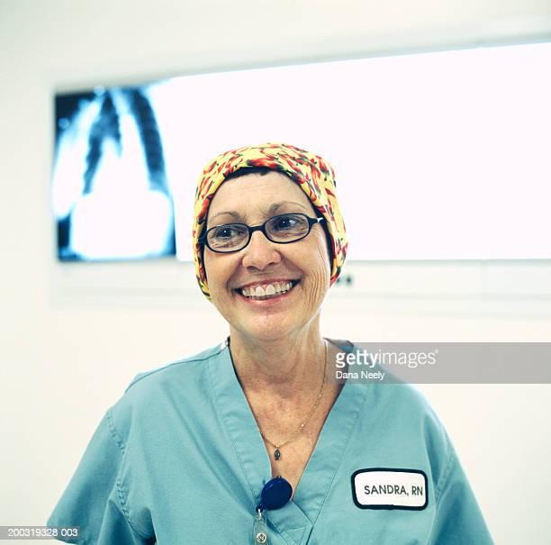 Senior female nurse smiling, X-ray on lightbox in background