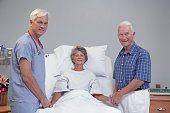 Senior female patient and husband smiling with doctor in hospital room