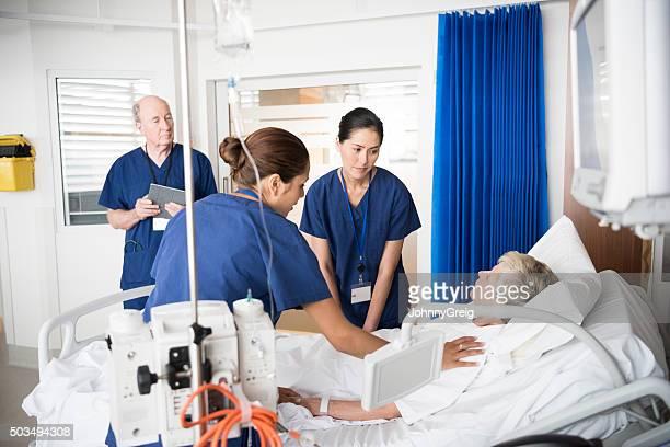 patient Senior femme au lit avec ce qui concerne le personnel médical