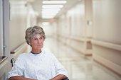 Senior female patient sitting in wheelchair at hospital corridor
