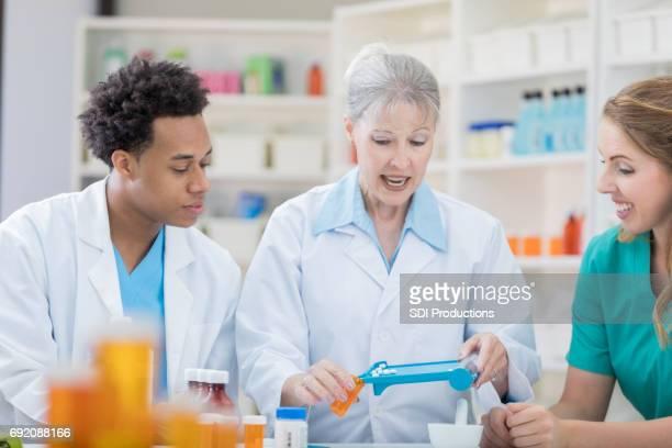 Senior vrouwelijke apotheker vult een patiënt recept