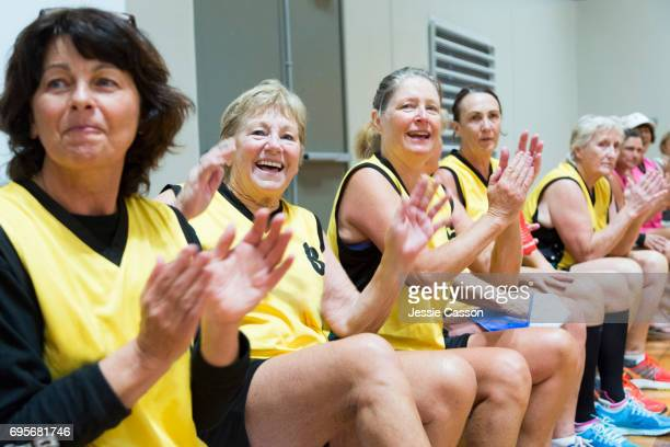 Senior female team players sitting and clapping on indoor court