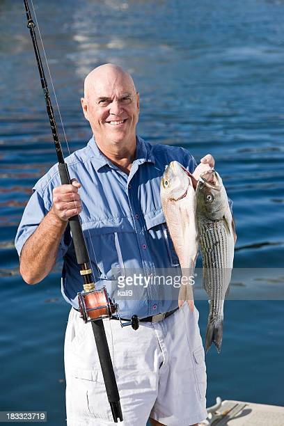 Senior fisherman with rod and fresh catch