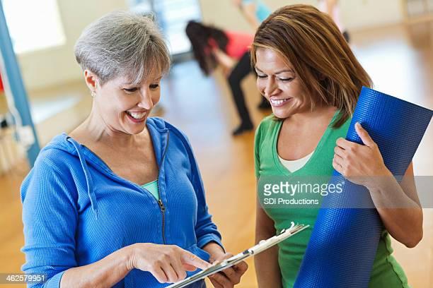 Senior instructor ayudar a estudiantes Inscríbase en una clase de ejercicio