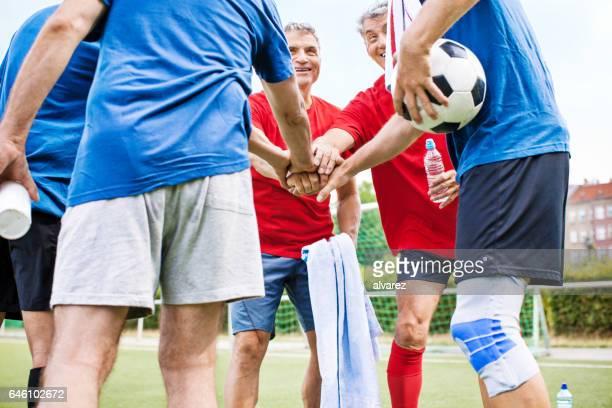 Setzen Sie ihre Hände zusammen Senior Football-Spieler