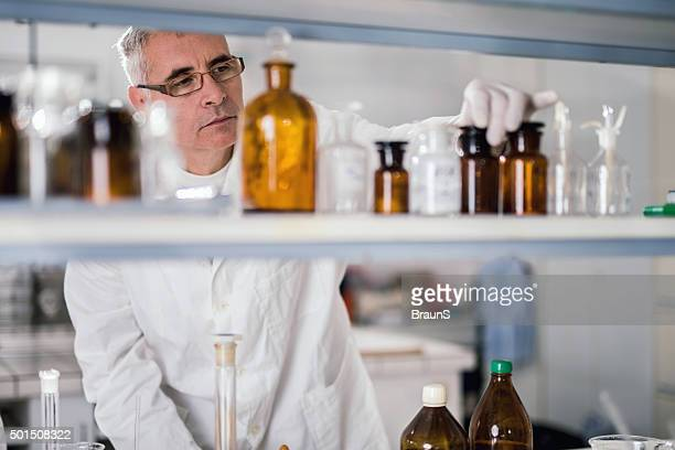 Senior forensic scientist choosing substances for his medical research.
