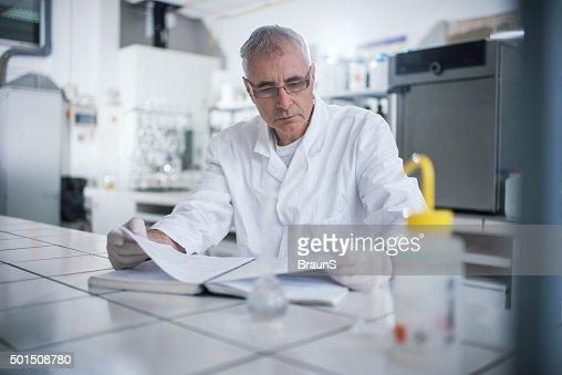 Senior forensic scientist reading medical data in laboratory.