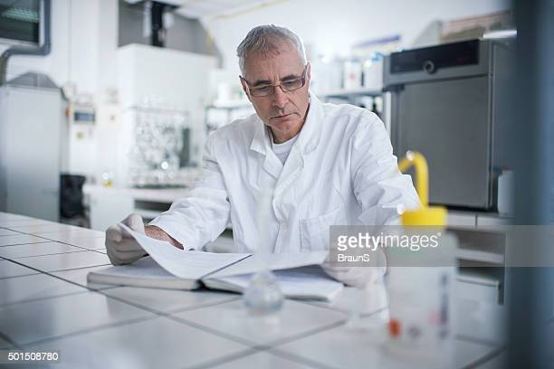 Senior forensic scientist reading medical data in laboratory.