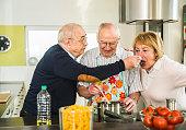 Senior friends cooking in kitchen