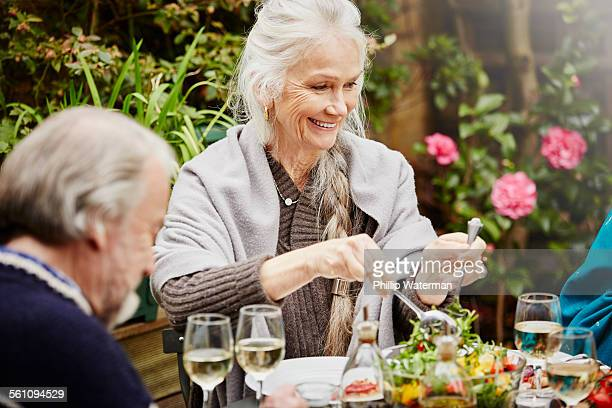Senior friends eating meal in garden