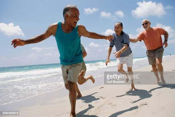 Senior friends jogging on beach