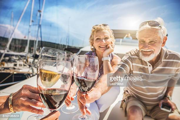 Senior amici brindando su uno yacht