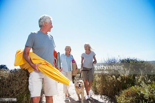 Senior friends with dog walking on beach path