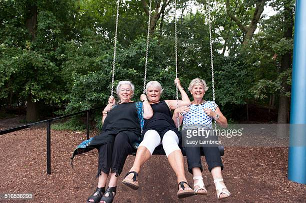 Senior girlfriends enjoying themselves on a swing