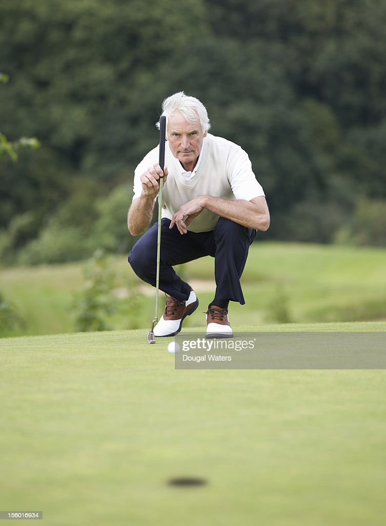 Senior golfer preparing to take shot on green. : Stock Photo