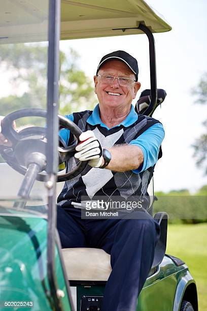 Ältere golfer sitzt in einem golf cart.