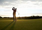 Senior golfer teeing off on golf course.