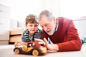 Senior grandfather with a small grandson at home playing with a car.