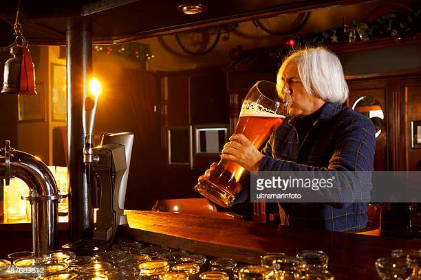 Senior gray-haired man drinking  huge glass of beer in pub