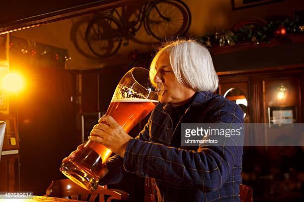 À poils courts Gris Senior homme buvant un grand verre de bière au pub