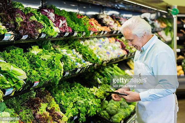 Senior grocery store manager taking inventory with digital tablet