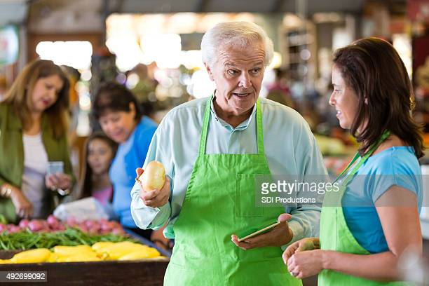 Senior grocery store owner training employee in produce section