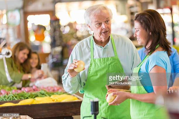 Senior grocery store owner training new employee