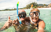 Senior happy couple taking selfie in tropical sea excursion with water camera - Boat trip snorkeling in exotic scenarios - Active retired elderly and fun concept around the world - Warm bright filter