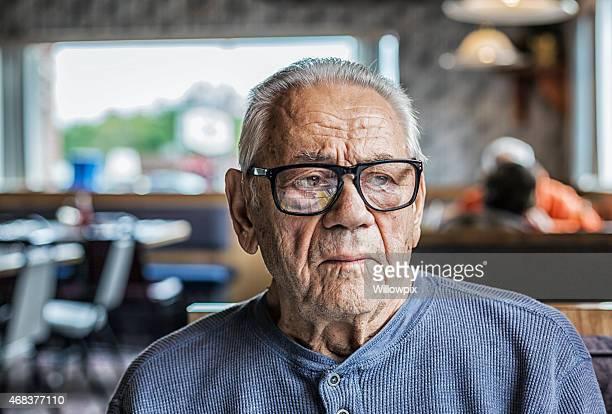 Senior Hearing Aid Man Serious Face Sitting in Restaurant