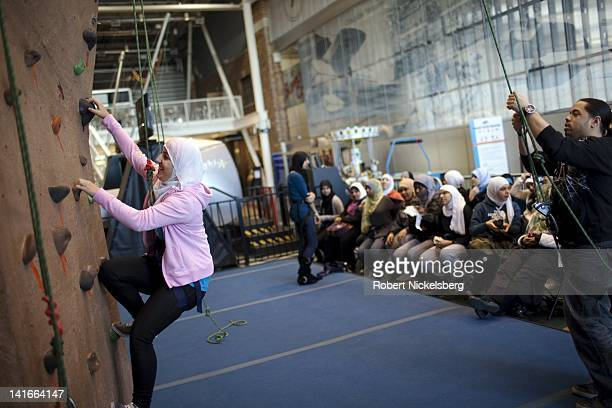 Senior high school girls at the Al Noor School try rock climbing at the Aviator Ice Hockey Rink February 16 2011 in the Brooklyn borough of New York...