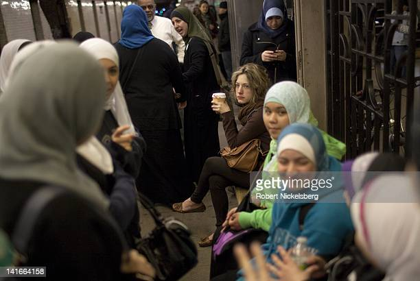 Senior high school girls at the Al Noor School wait for a subway while on a class trip April 15 2011 in the Brooklyn borough of New York A nonMuslim...