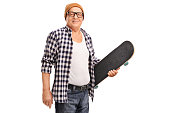Studio shot of a senior hipster with a yellow hat holding a skateboard and looking at the camera isolated on white background