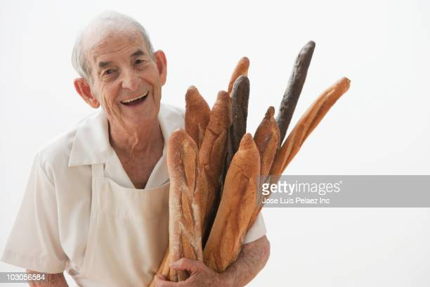 Senior Hispanic baker holding loaves of bread