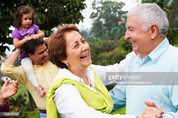 Senior Hispanic couple dancing outdoors