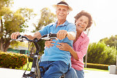 Senior Hispanic Couple Riding Bikes In Park Smiling To Camera