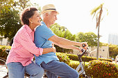 Senior Hispanic Couple Riding Bikes In Park Smiling