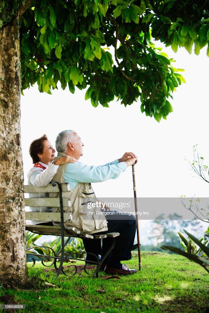 Senior Hispanic couple sitting on park bench : Stock Photo